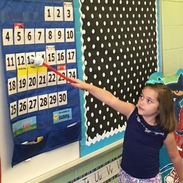 VPK student in classroom pointing to number board