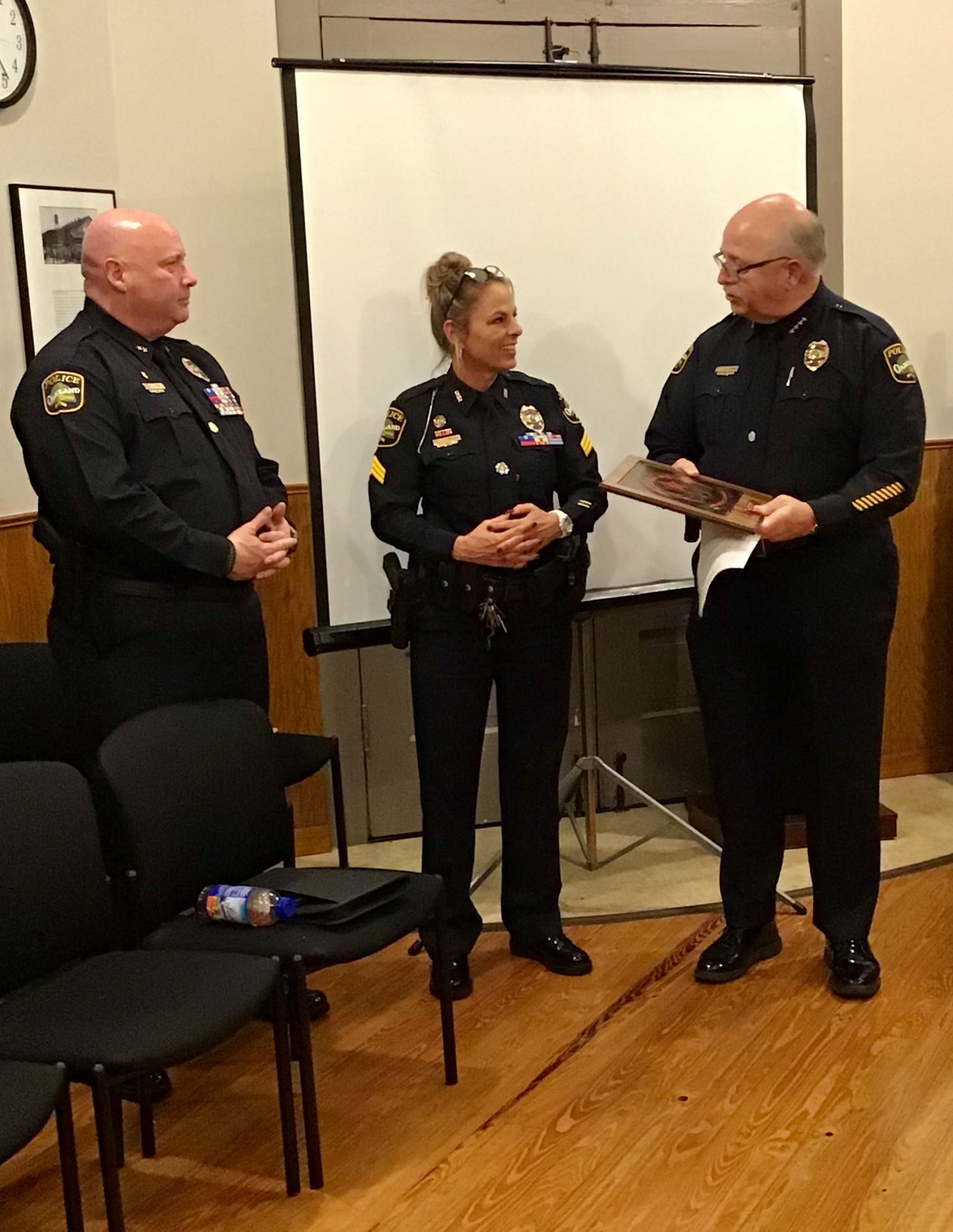 Chief Thomas presents plaque to Sergeant Campbell while Deputy Chief Peek looks on