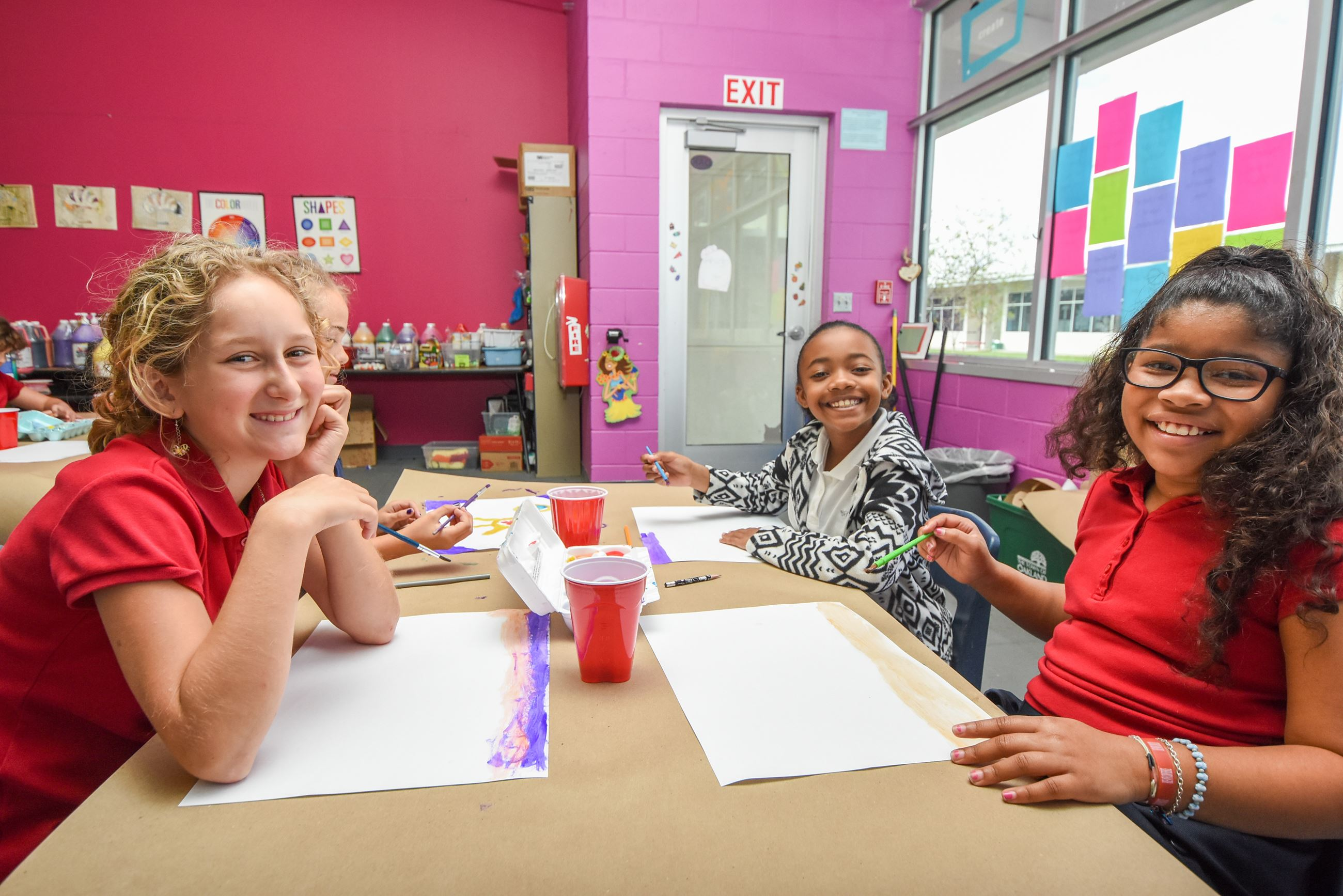 A group of girls painting in the Art classroom.